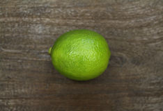 Whole green lime on dark wooden surface. Fresh whole lime fruit shot from above on a dark wooden surface Royalty Free Stock Image