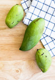 Whole Green Mango on a wooden table.In selective focus. Royalty Free Stock Image