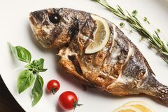 Whole grilled dorado and sea bass on table. Restaurant food - whole grilled dorado and sea bass on wooden restaurant table, mediterranean cuisine, copy space royalty free stock images