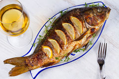 Whole grilled fish carp. Served with salad and lemon; glass of wine Stock Image