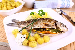 Whole grilled fish served with potatoes, lemon and sauce Stock Photo