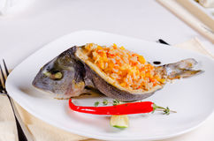 Whole grilled fish stuffed with savory rice Royalty Free Stock Images