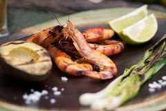 Whole Grilled Shrimps Dinner in Garden. Plate of grilled shrimps, avocado, and scallions. Served with lime ans sea salt. Outside dinner in a garden Stock Photo