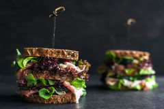 Whole grin bread sandwiches. Big toast sandwich with lettuce and prosciutto royalty free stock photography