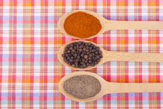 Whole and ground pepper in a wooden spoon Stock Photos