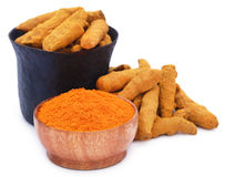 Whole and ground turmeric with mortar and pestle Royalty Free Stock Images