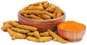 Whole and ground turmeric in wooden bowls Royalty Free Stock Photos