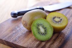 Whole and haft cut green and golden kiwi on board Royalty Free Stock Photos