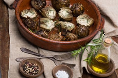 Whole and half artichokes roasted simply Stock Photo