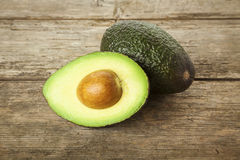 Whole and half avocado on rustic wood Royalty Free Stock Photo