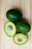 Whole and half avocado. On wood background Stock Image