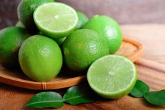 Whole and half cut fresh lime in bamboo basket and on wooden background royalty free stock photo