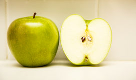 Whole and Half Green Apple on Countertop Royalty Free Stock Photo