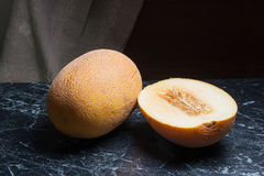 Whole and half honeydew melon fruit on dark marble background. Stock Photo