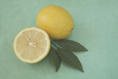 Whole and half lemon with leaves Royalty Free Stock Photography