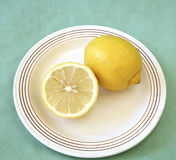 Whole and half lemon on plate Stock Images