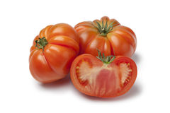 Organic whole and half Coeur de Boeuf tomatoes Stock Photography