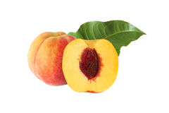 Whole and half peach with stone and leaf isolated. On white background Royalty Free Stock Image