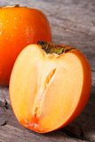 Whole and half persimmon closeup on a wooden table. Stock Images