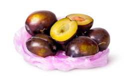 Whole and half violet plums in plastic bag Stock Photos