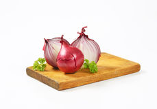 Whole and halved red onions Stock Images