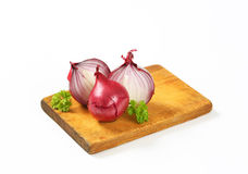 Whole and halved red onions Stock Image