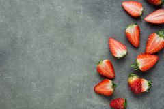 Whole and Halved Ripe Organic Strawberries Scattered on Black Stone Background Arranged in Border. Vitamins Healthy Lifestyle stock photography