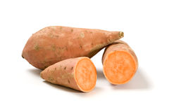 Whole and halved sweet potatoes Royalty Free Stock Image