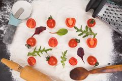 Whole and halved tomatoes on flour, arugula and basil stock images