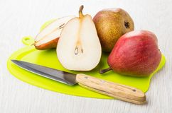 Whole and halves of red pears, kitchen knife on cutting board on wooden table. Whole and halves of red pears, kitchen knife on plastic cutting board on wooden stock photo