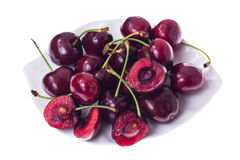 Whole and halves of ripe cherries on white plate Royalty Free Stock Photography