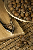 Whole hazelnuts in a wooden bowl. Hazelnuts in a wooden bowl with a nutcracker on the table Royalty Free Stock Photo
