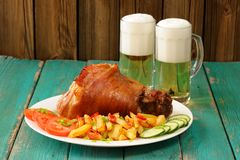 Whole homemade Eisbein with foamy beer, french fries, cucumbers Stock Photo