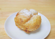 Whole homemade Japanese choux cream puff with icing on a small white plate Royalty Free Stock Images