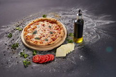 Whole italian delicious fresh pizza with tomato and pepperoni on a dark background.  Pizza on the black table. with ingredients Stock Images