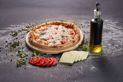 Whole italian delicious fresh pizza with tomato and pepperoni on a dark background.  Pizza on the black table. with ingredients Royalty Free Stock Photos