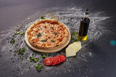 Whole italian delicious fresh pizza with tomato and pepperoni on a dark background.  Pizza on the black table. with ingredients Stock Photos