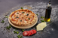 Whole italian delicious fresh pizza with tomato and pepperoni on a dark background.  Pizza on the black table. with ingredients Stock Image
