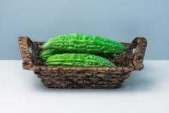Whole karela bitter melon caraili studio close up blue background inside straw basket Stock Photography