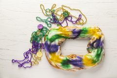 Whole King Cake with Mardi Gras Beads. A whole king cake overhead view, a tradition in New Orleans for Mardi Gras with beads stock photos