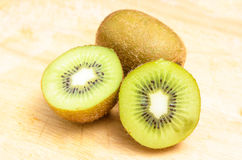 Whole kiwi fruit and his sliced segments Stock Photography
