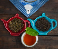 Whole leaf tea with teapot and cup with mint on wooden table Stock Image