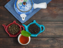 Whole leaf tea with teapot and cup on wooden table Stock Images