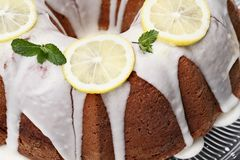 Whole Lemon Bundt Cake Abstract. Whole lemon cream cheese bundt cake with slices of fresh lemons and mint on top. Extreme shallow depth of field with selective stock photos