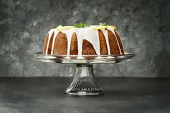 Whole Lemon Bundt Cake in Center of Dark Background. Whole lemon cream cheese bundt cake with slices of fresh lemons and mint on top. Extreme shallow depth of stock photography