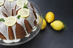 Whole Lemon Bundt Cake on a Stand. Whole lemon cream cheese bundt cake with slices of fresh lemons and mint on top. Extreme shallow depth of field with selective stock photos