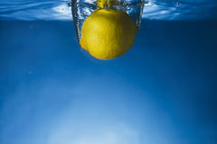 Whole lemon dropped in water Stock Image