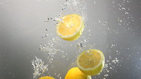 Whole lemon drops under water. Isolated stock video