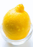 Whole lemon in the glass bowl Stock Image