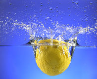 A whole lemon splashing into water. With a blue background and a large splash Stock Image